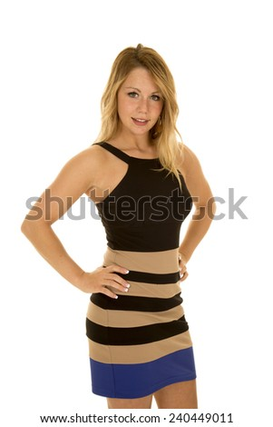 A woman in her black and tan dress with her hands on her hips. - stock photo