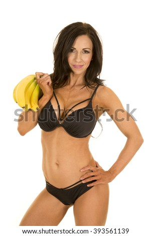 A woman in her black bikini with a smile holding onto bananas. - stock photo