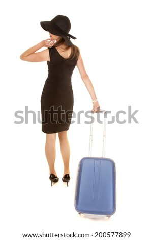 A woman in her black dress pulling on her suitcase going on a trip.