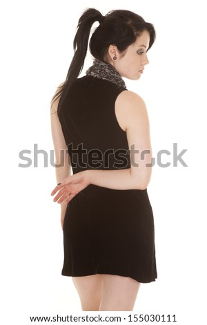 A woman in her black dress with her hand behind her back looking down. - stock photo