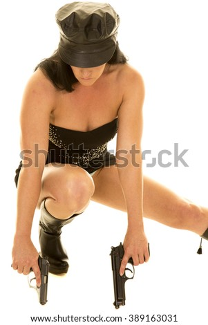 A woman in her black leather dress and hat, holding on to pistols crouched down - stock photo