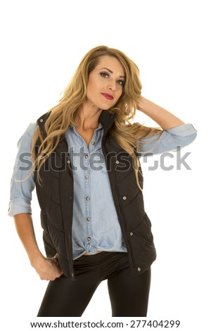 A woman in her black vest and jean shirt, playing with her hair. - stock photo