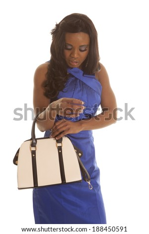 A woman in her blue dress looking down into her purse. - stock photo