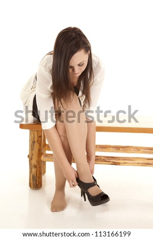 A woman in her business clothes leaning over fixing her shoe while sitting on a bench - stock photo