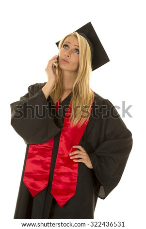 a woman in her cap and gown on her cell phone. - stock photo
