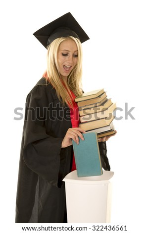 a woman in her cap and gown throwing away all her books in the garbage can. - stock photo