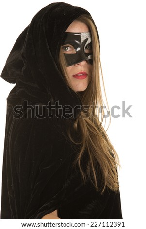 a woman in her cloak and mask hiding. - stock photo
