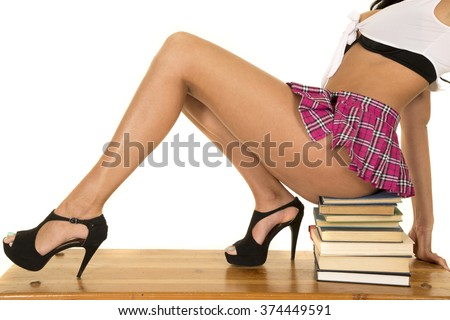 A woman in her costume sitting on a stack of books.