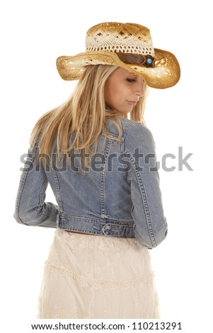 A woman in her cowgirl hat and jean jacket looking over her shoulder.