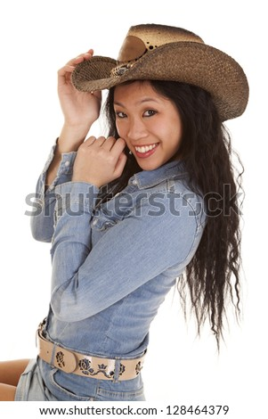A woman in her cowgirl hat with a big smile on her face.