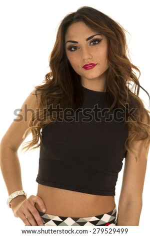 A woman in her crop top with her hand on her hip with a serious expression. - stock photo