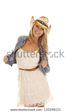 A woman in her denim jacket and her lace dress with a smile on her face. - stock photo