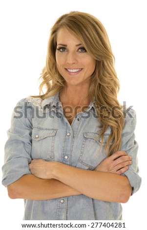 A woman in her denim top with her arms folded and a smile. - stock photo