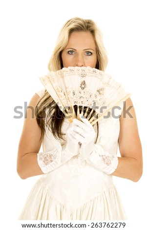 a woman in her fancy dress, looking over her fan, sneaking a peek. - stock photo