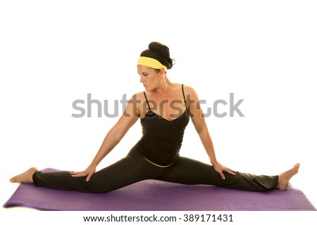 A woman in her fitness clothing doing the splits. - stock photo