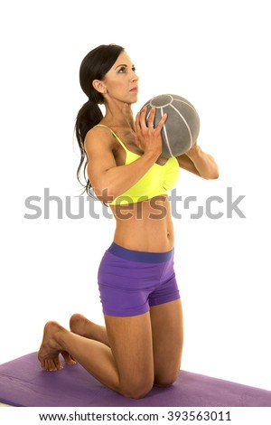 A woman in her fitness clothing on her knee on her fitness mat with her medicine ball working out. - stock photo