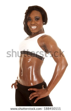 a woman in her fitness clothing with her hands on her hips,
