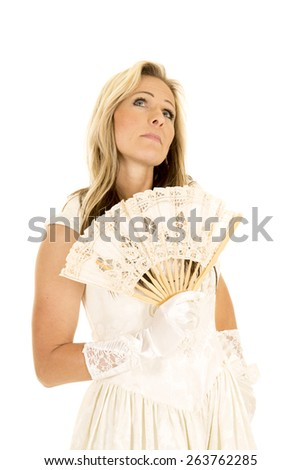 a woman in her formal wedding dress holding on to a white fan. - stock photo