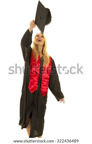 a woman in her graduation cap and gown throwing up her cap in the air.