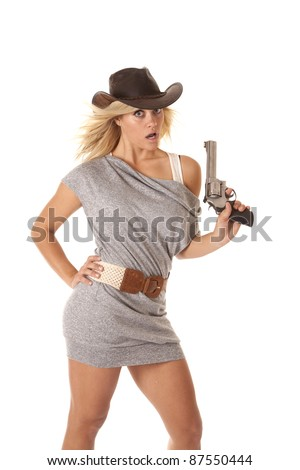 A woman in her gray short dress with  a western hat and holding a pistol with  a shocked expression.