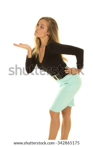 A woman in her green pencil skirt and black top, blowing a kiss. - stock photo