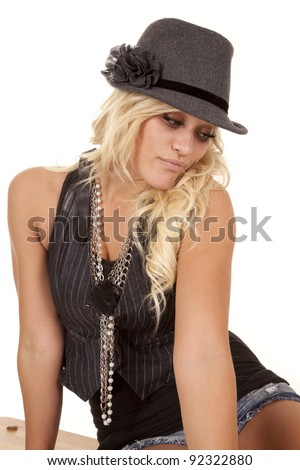A woman in her hat and nice vest sitting and looking down.