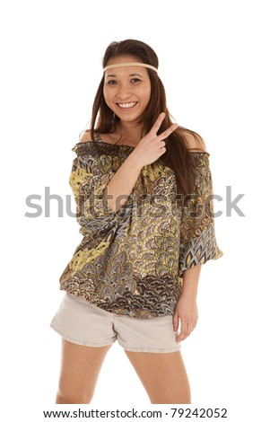 A woman in her hippie outfit showing the peace sign.