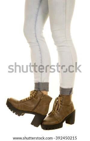 A woman in her jeans standing up with her boot on the other one.
