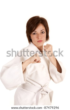 A woman in her karate outfit with her fists ready to fight with an expression of anger.