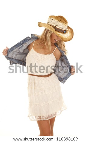 A woman in her lace dress holding out her jacket looking down with a smile on her face. - stock photo