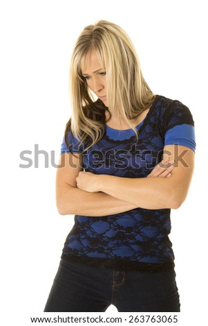 a woman in her lace top, and jeans, looking down with an upset expression. - stock photo