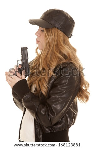 A woman in her leather jacket and hat blowing on the tip of her gun.