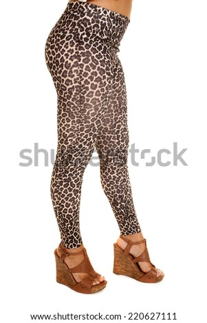 A woman in her leopard printed leggings wearing shoes. - stock photo