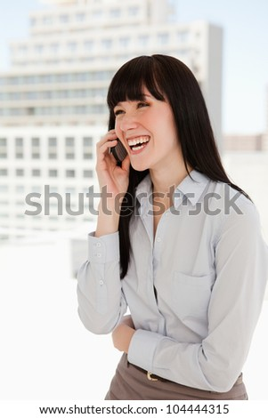 A woman in her office at work laughing on her mobile phone - stock photo