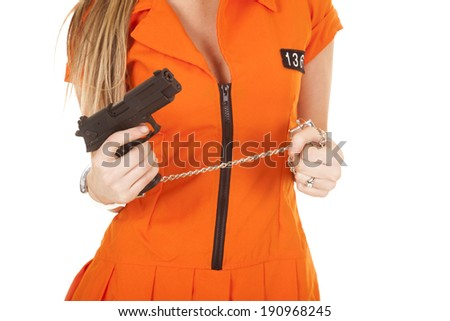a woman in her orange jump suit wearing hand cuffs. - stock photo