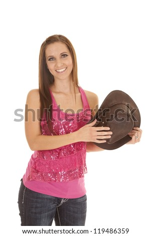 a woman in her pink tank holding on to her cowgirl hat. - stock photo