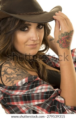 A woman in her plaid shirt, and western hat, with her tattoos showing. - stock photo