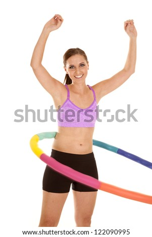 A woman in her purple sports bra and shorts working out with a weighted hoola hoop