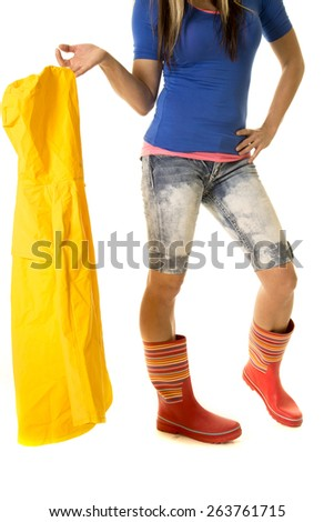a woman in her rain boots, holding on to her raincoat. - stock photo