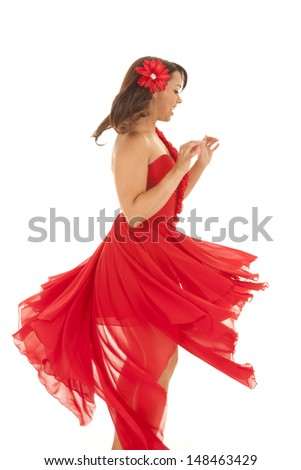 a woman in her red dress spinning in a circle and dancing around. - stock photo