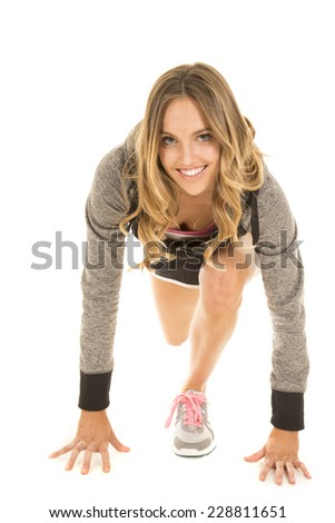 a woman in her running stance with a smile on her face. - stock photo