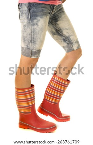 a woman in her shorts and rain boots, ready for the puddles. - stock photo