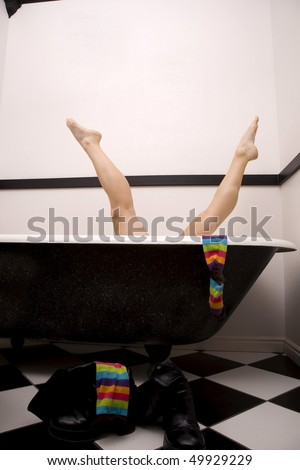 A woman in her tub playing around putting her legs up in the air in the splits, with her colorful striped socks hanging off the tub and her black boots on the floor. - stock photo