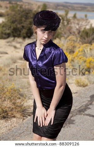 A woman in her vintage clothing looking at the camera. - stock photo