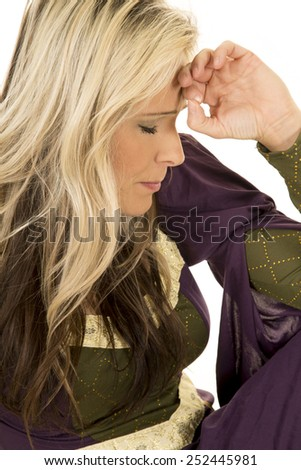 A woman in her vintage dress with a somber expression with her hand on her head. - stock photo
