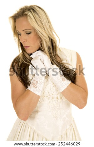 A woman in her vintage wedding dress with her hands up by her face, looking to the side with a sad expression. - stock photo