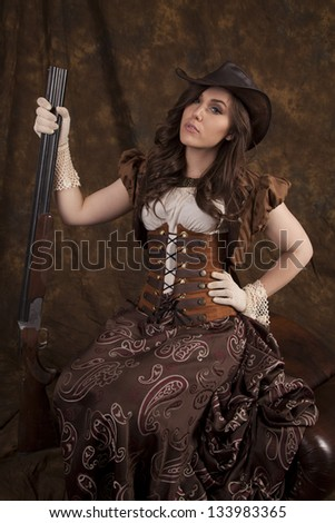 a woman in her vintage western dress holding on to a shotgun with a serious expression on her face.
