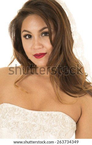 A woman in her wedding dress and veil with a small smile on her lips - stock photo