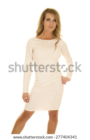 A woman in her white fitted dress, with her hand on her hip, and a smile on her lips. - stock photo