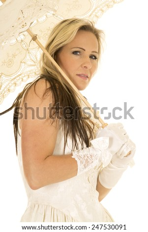 a woman in her white wedding dress with white gloves and holding on to a lace umbrella. - stock photo